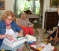 L to R: Claudia Crews opening items she knitted; Ann Herlich (sitting)